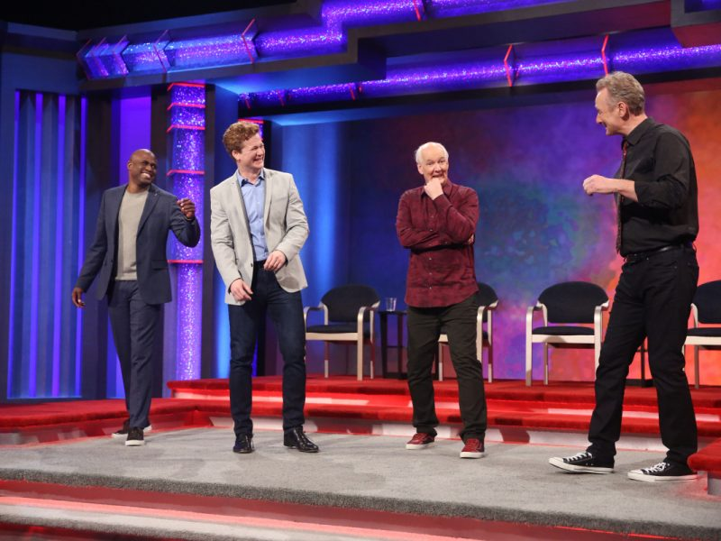 "Whose Line Is It Anyway? -- ""Jonathan Mangum 4"" -- Image WL611_ Jonathan Mangum 4_0006.jpg -- Pictured (L-R) Wayne Brady, Jonathan Mangum, Colin Mochrie and Ryan Stiles -- Photo: Patrick Wymore/The CW -- © 2018 The CW Network, LLC. All Rights Reserved"
